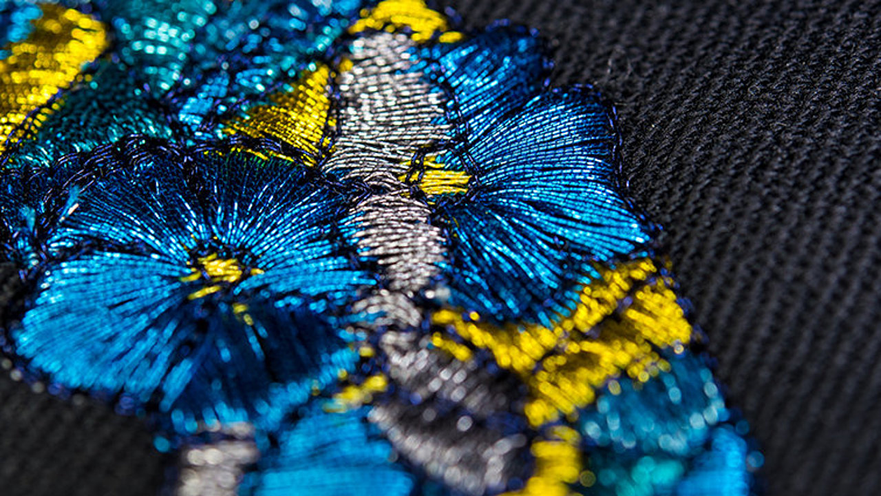[Translate to Englisch IND:] blue and gold metallic thread embroidery of petals